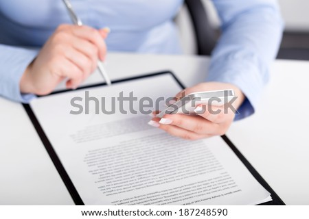 Young woman working with a mobile phone and holding a pen over contract - stock photo