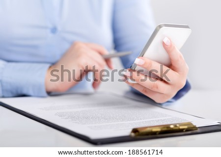 Young woman working with a mobile phone and holding a pen over contract