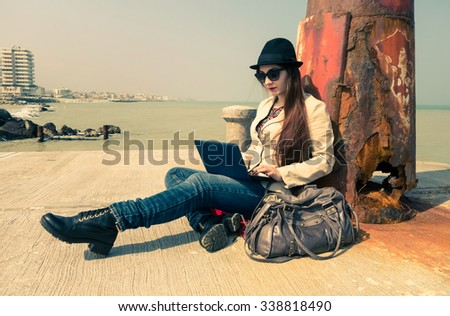 Young woman working with pc outdoor - Lonely girl writing using laptop wifi connected - Teenager model sitting next to old lighthouse on the dock of the bay - Misty vintage filtered look retro style - stock photo