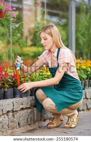 Young woman working with shovel in her garden in spring - stock photo