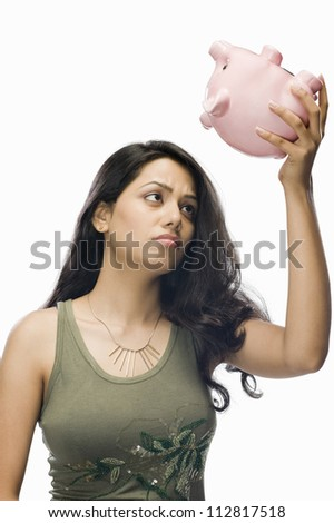 Young woman worried with a piggy bank - stock photo