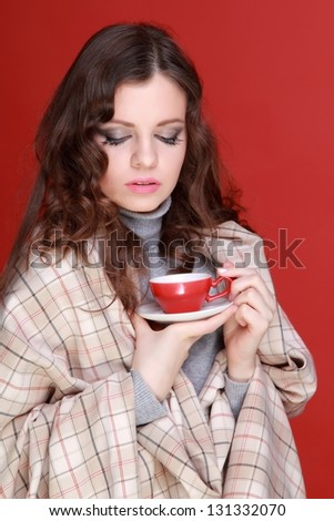 Young woman wrapped in a blanket and drinking morning coffee on Food and Drink