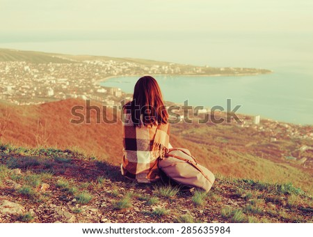 Young woman wrapped in plaid sitting on peak of mountain and enjoying view of sea. Image with instagram filter