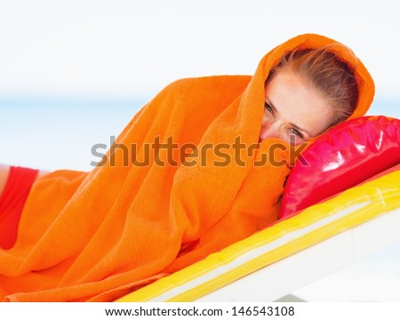 Young woman wrapped in towel laying on chaise-longue