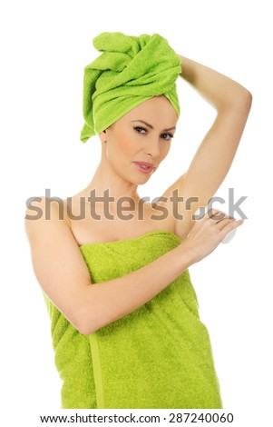Young woman wrapped in towel using deodorant. - stock photo