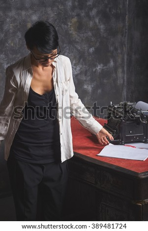 Young woman writer in creative thinking process, retro typewriter on old retro table, art space - stock photo