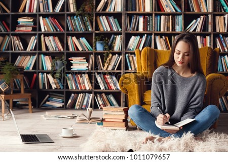 Young woman writer in library at home creative occupation sitting writing notes