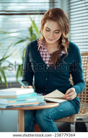 Young woman writing in a notebook - stock photo