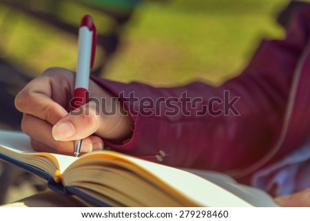 Young woman writing notes sitting on the bench - stock photo