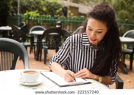 young woman writing on a clipboard with a coffee. - stock photo