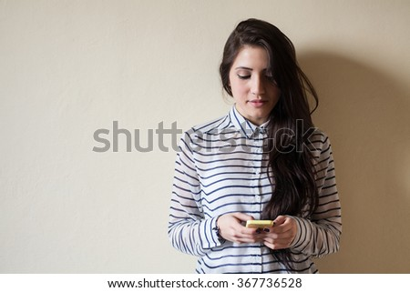 Young woman (18 years, mixed race Asia/Caucasian) looking at mobile phone. - stock photo