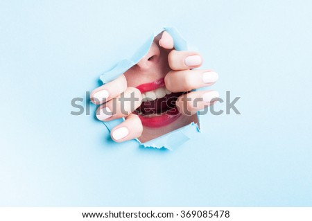 Young woman yelling thru cut out blue or turquoise cardboard with copyspace - stock photo