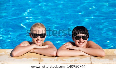 young womans in swimwear by the pool