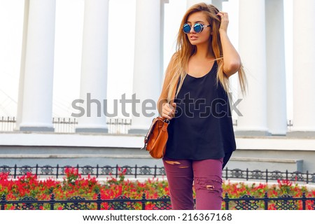 Young womb walking alone after shopping at the street at nice day, wearing stylish casual clothes and sunglasses. - stock photo