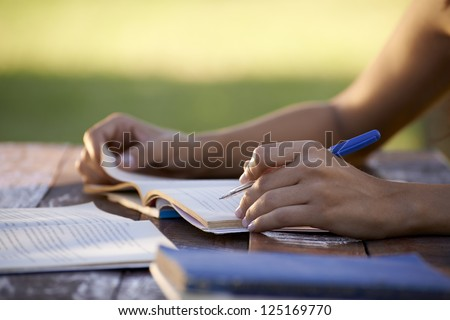 Young women and education, close up of hands of girl studying for college exam in park. Side view, copy space - stock photo