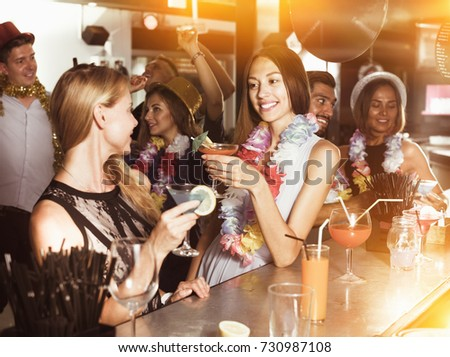 Young women are drinking cocktails on hawaiian party in bar