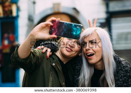 Young women best friends having fun taking a selfie