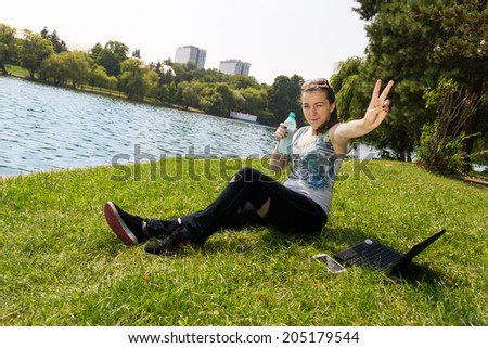 young women blinking showing victory sign - stock photo
