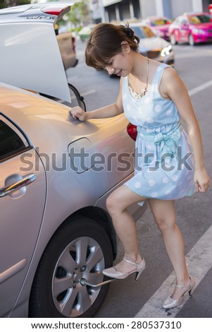 Young women changing tire on side of the road. Portrait of Asia - stock photo