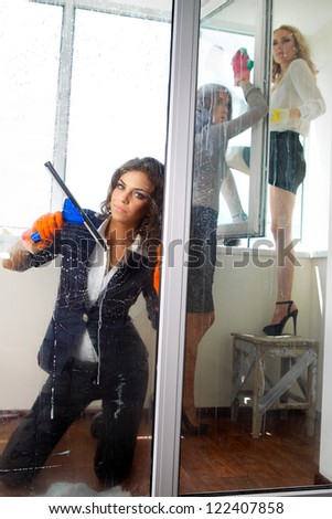 Young women cleaning her windows with squeegee cleaning - stock photo