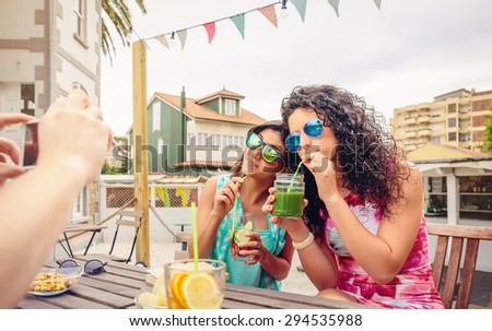 Young women couple with sunglasses drinking healthy drinks while their friend taking a photo with his smartphone in a summer day outdoors.  Young people lifestyle concept. - stock photo