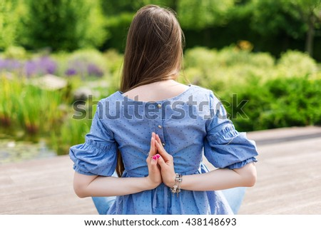 Young women do yoga outdoors. Girl sitting in easy pose and meditating in the park, view from the back, no face.