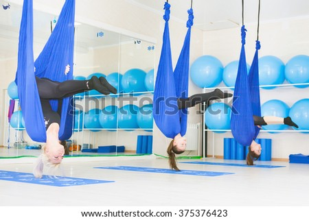 Young women doing aerial yoga exercise or antigravity yoga indoor. Fitness, stretch, balance, exercise and healthy lifestyle people. Woman using hammock.