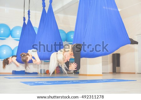 Young women doing aerial yoga exercise or antigravity yoga indoor. Flying, fitness, stretch, balance, exercise and healthy lifestyle people. Woman using hammock.