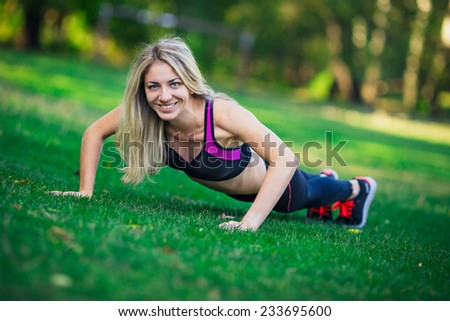 Young women doing push-ups in the park - stock photo