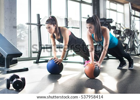 Young women doing stretching exercises on fitness ball in gym.