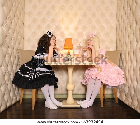 Young women dressed as dolls, sitting at a table in the doll house.