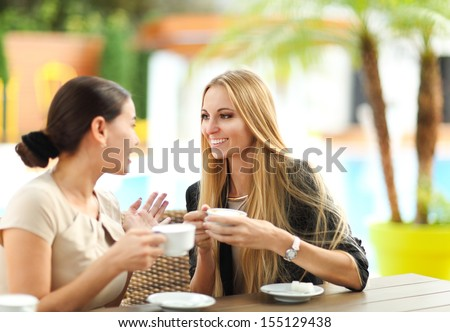 Young women drinking coffee in a cafe outdoors. Shallow depth of field - stock photo