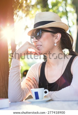 Young women drinking coffee in a cafe outdoors. Small depth of field. Lens flare blur. Soft focus - stock photo