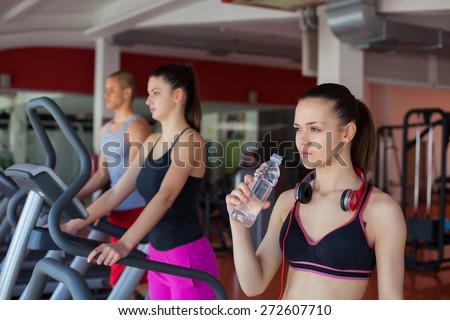 young women drinking water after sports. Fitness gym. - stock photo