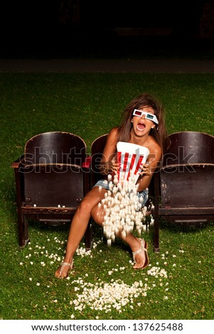 young women eat popcorn in to the summer cinema