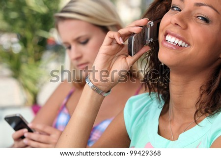 Young women embracing technology - stock photo