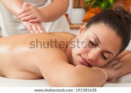 Young women getting back massage in massage salon.