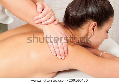 Young women getting back massage in massage salon. - stock photo
