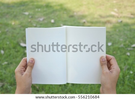 young women hold and open notebook from two hands , background green nature