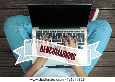 Young women holding laptop writen Benchmarking on it