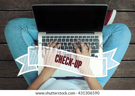 Young women holding laptop writen Check-Up on it - stock photo