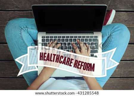 Young women holding laptop writen Health Care Reform on it - stock photo