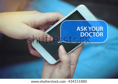 Young women holding mobile phone writen Ask Your Doctor on it - stock photo