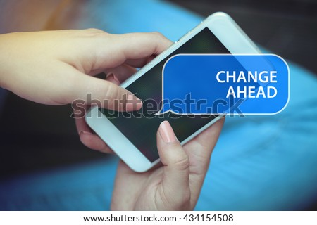 Young women holding mobile phone writen Change Ahead on it - stock photo