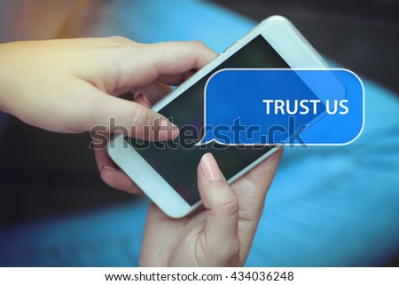 Young women holding mobile phone writen Trust Us on it - stock photo