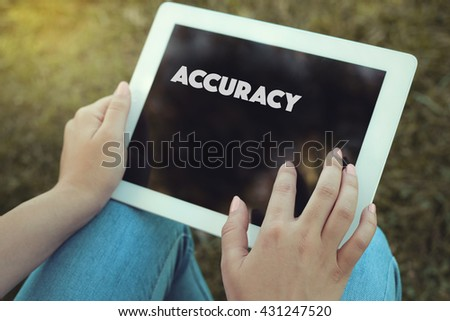 Young women holding tablet writen Accuracy on it - stock photo