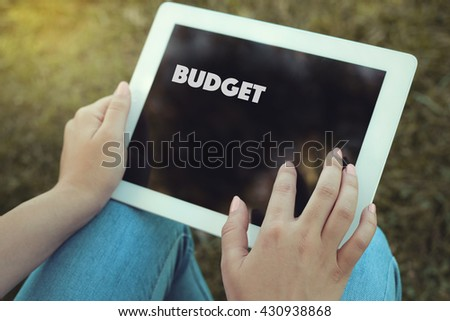 Young women holding tablet writen Budget on it - stock photo