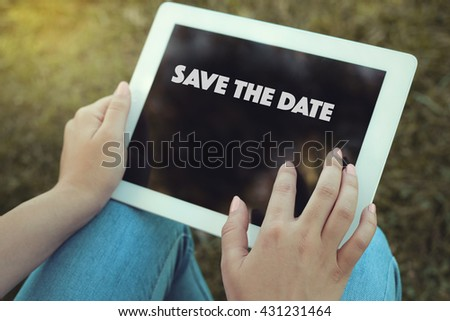 Young women holding tablet writen Save The Date  on it - stock photo