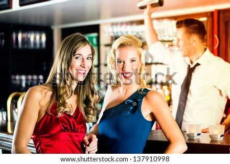 Young women in bar or club, the bartender is mixing cocktails - stock photo