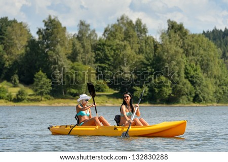 Young women in bikinis kayaking on river summertime - stock photo